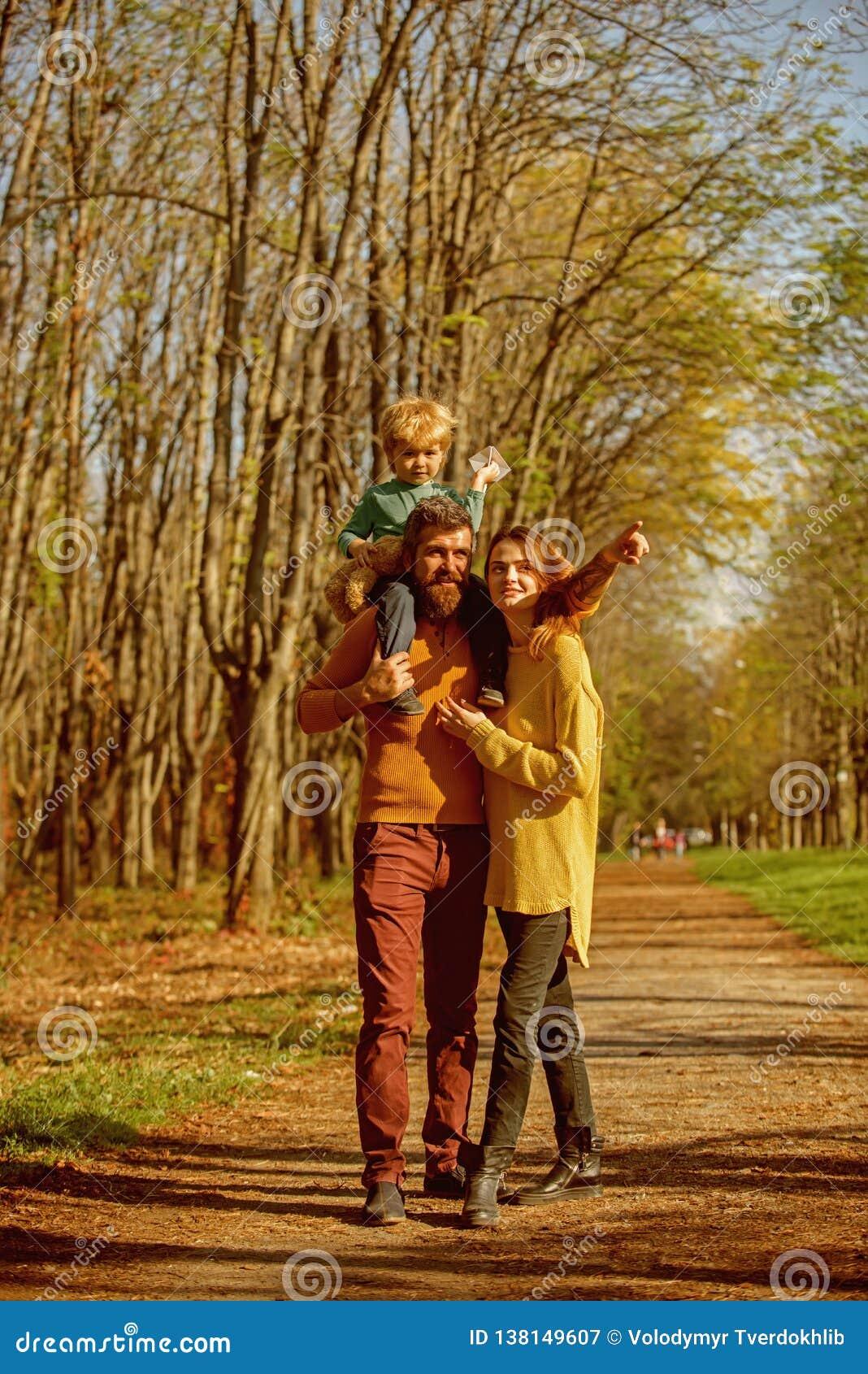 Madre y padre que llevan a cuestas al pequeño hijo que juega con el avión de papel con la inspiración La familia es fuente de ins