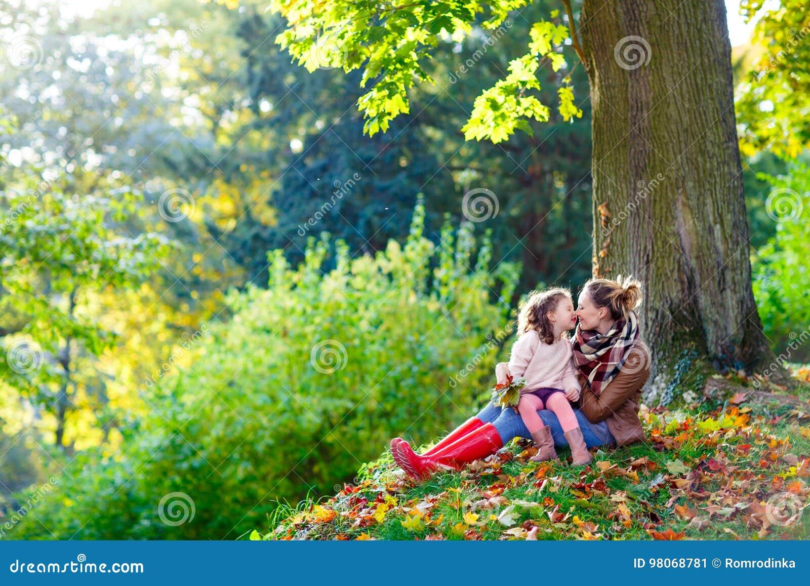 Madre y pequeña hija en el bosque hermoso del otoño