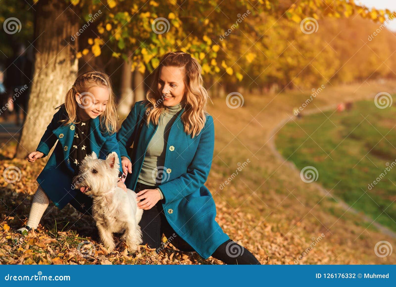 Madre y pequeña hija que caminan con el perro en otoño Retrato del aire libre de la familia feliz Autumn Fashion Pequeña hija ele