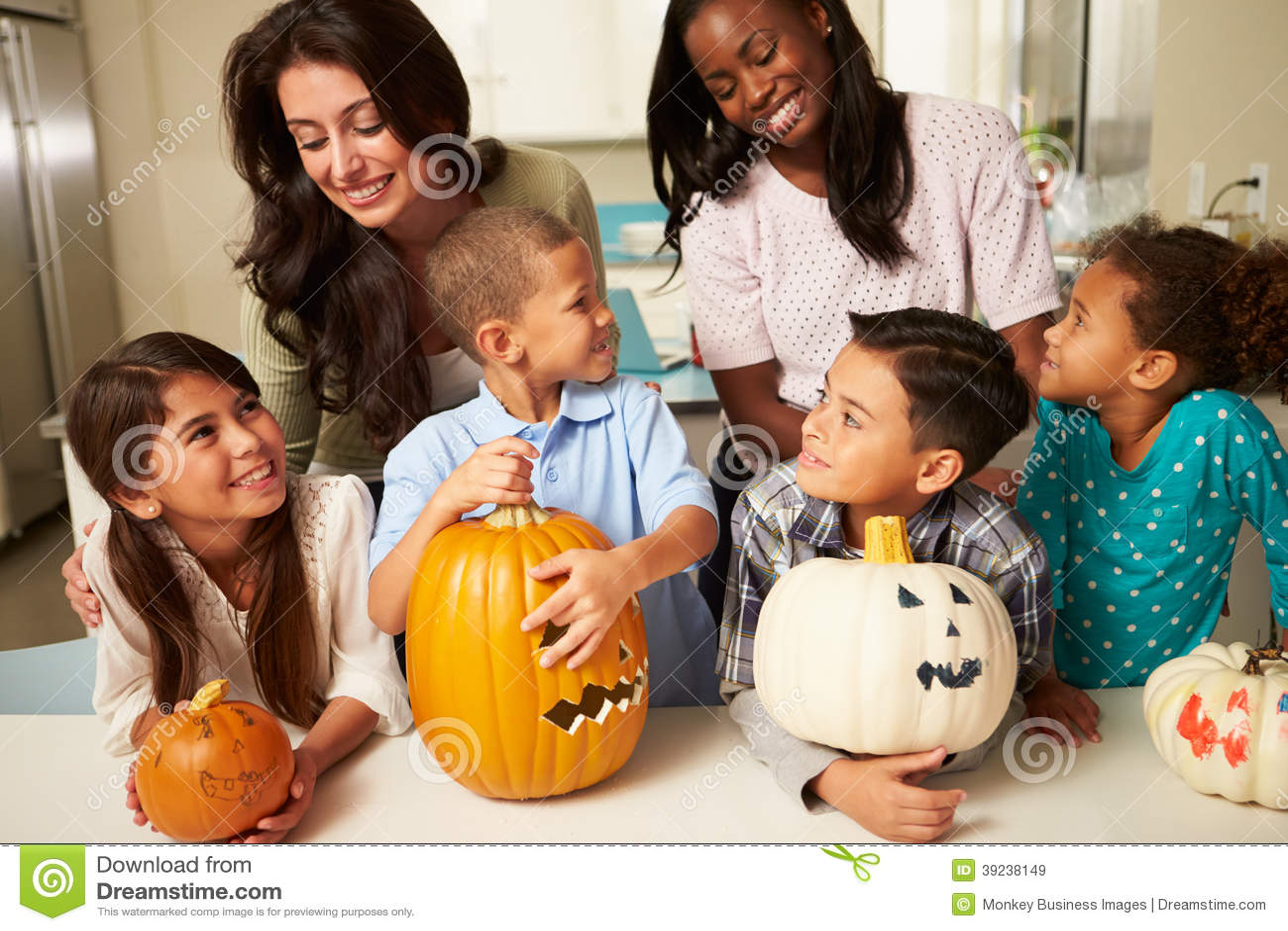 Madri e bambini che fanno le lanterne di Halloween
