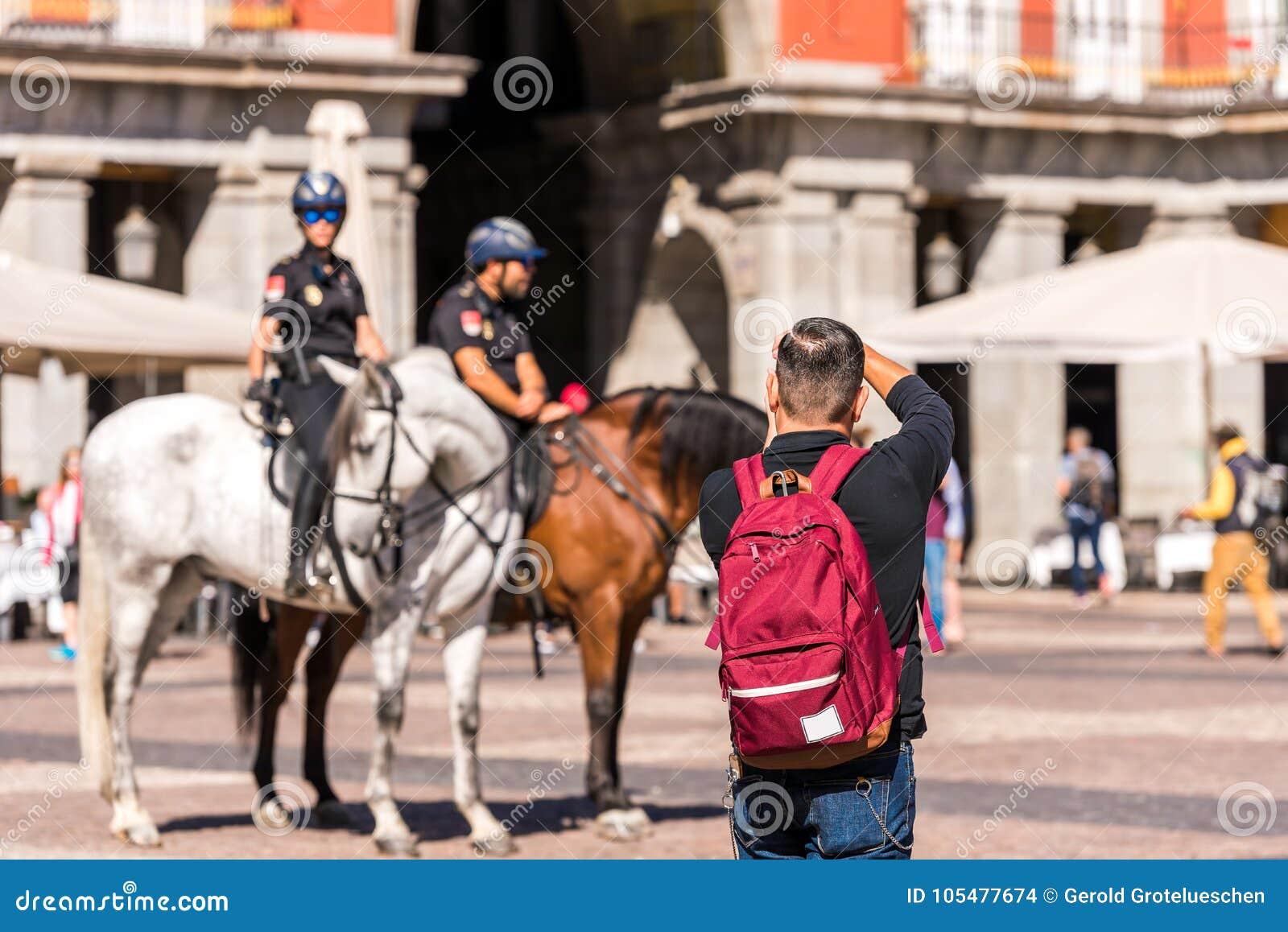 MADRID, SPANIEN - 26. SEPTEMBER 2017: Ein Mann fotografiert die berittene Polizei im Quadrat des Royal Palace-Gebäudes