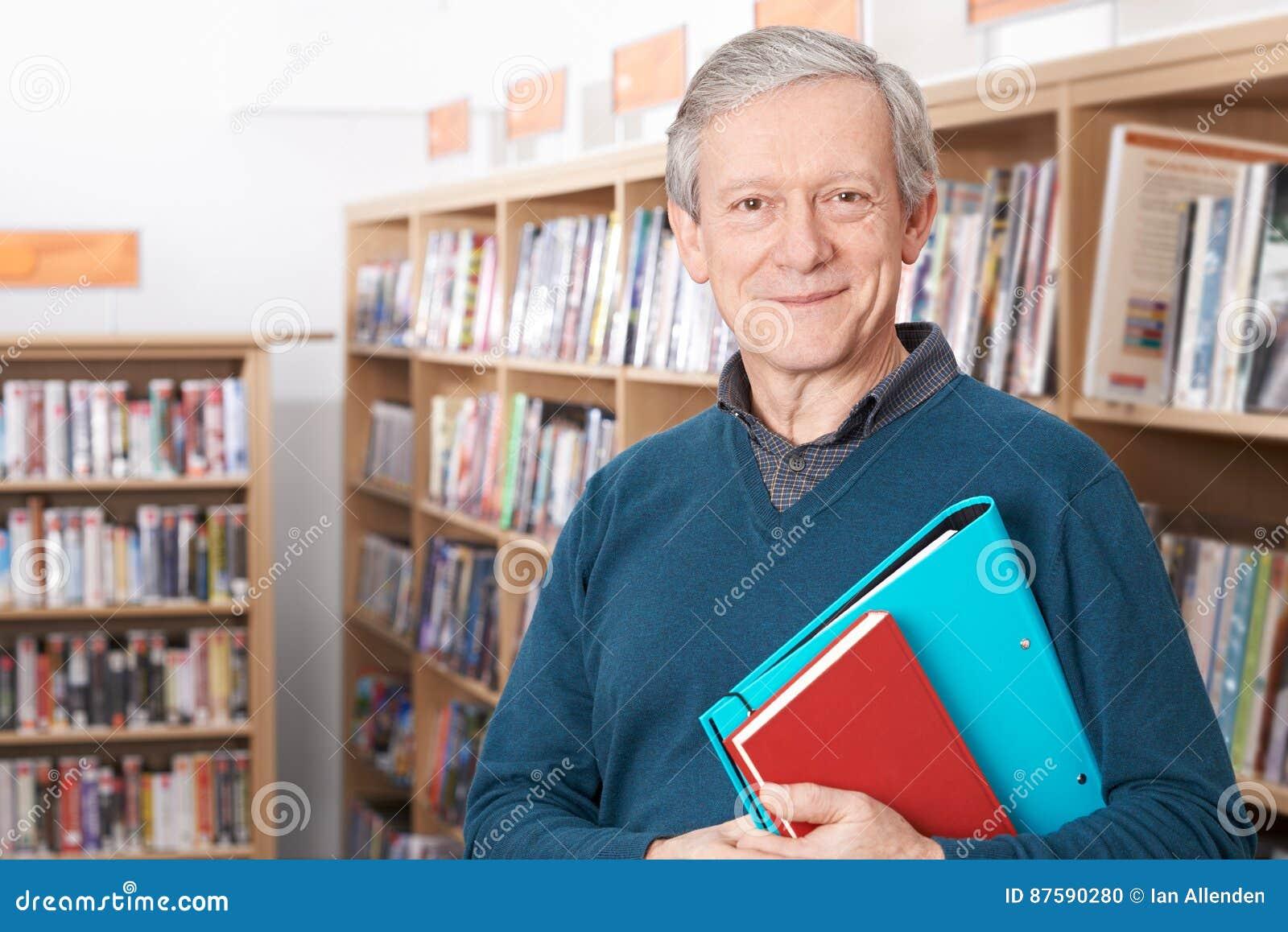 Madure al estudiante masculino que estudia en biblioteca