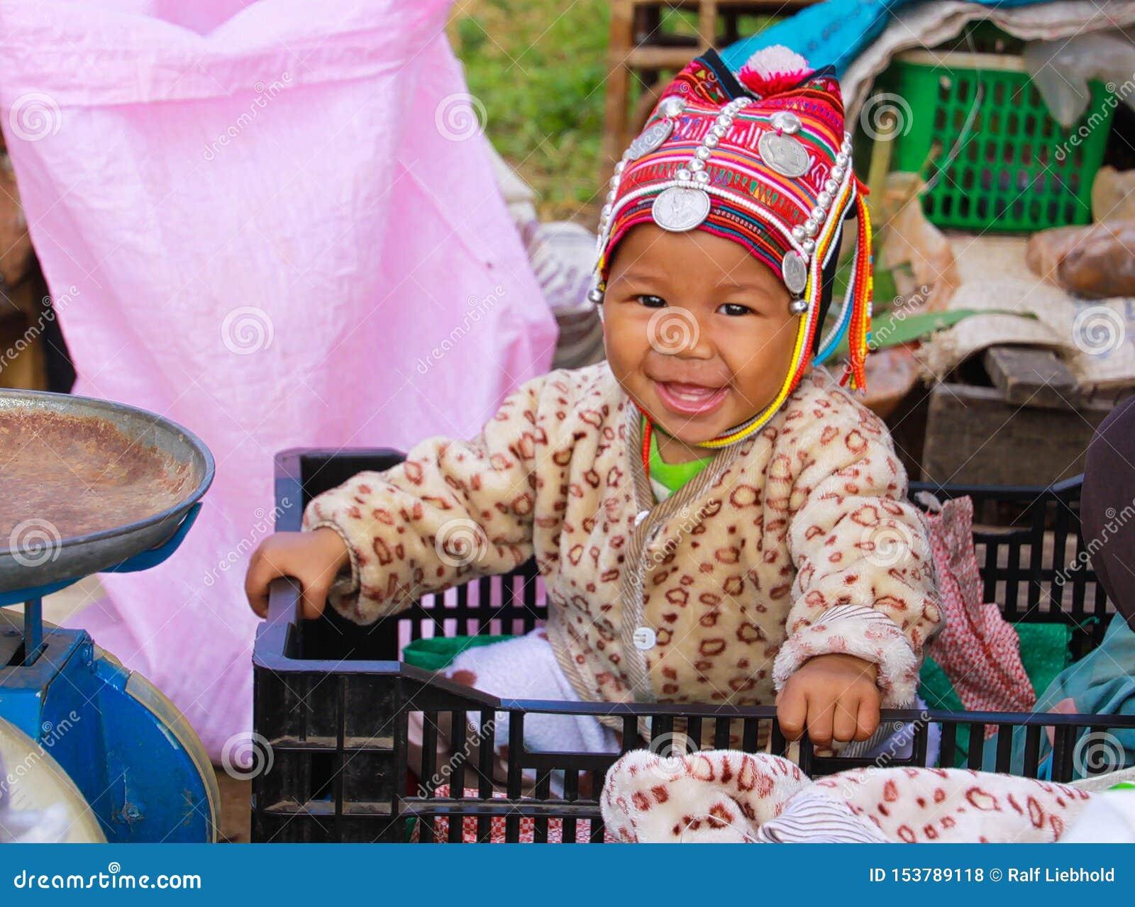 MAE SALONG, ΤΑΪΛΆΝΔΗ - 17 ΔΕΚΕΜΒΡΊΟΥ 2017: Πορτρέτο ενός ευτυχούς μωρού μικρών παιδιών από τη φυλή λόφων Akha σε ένα κιβώτιο αγορ