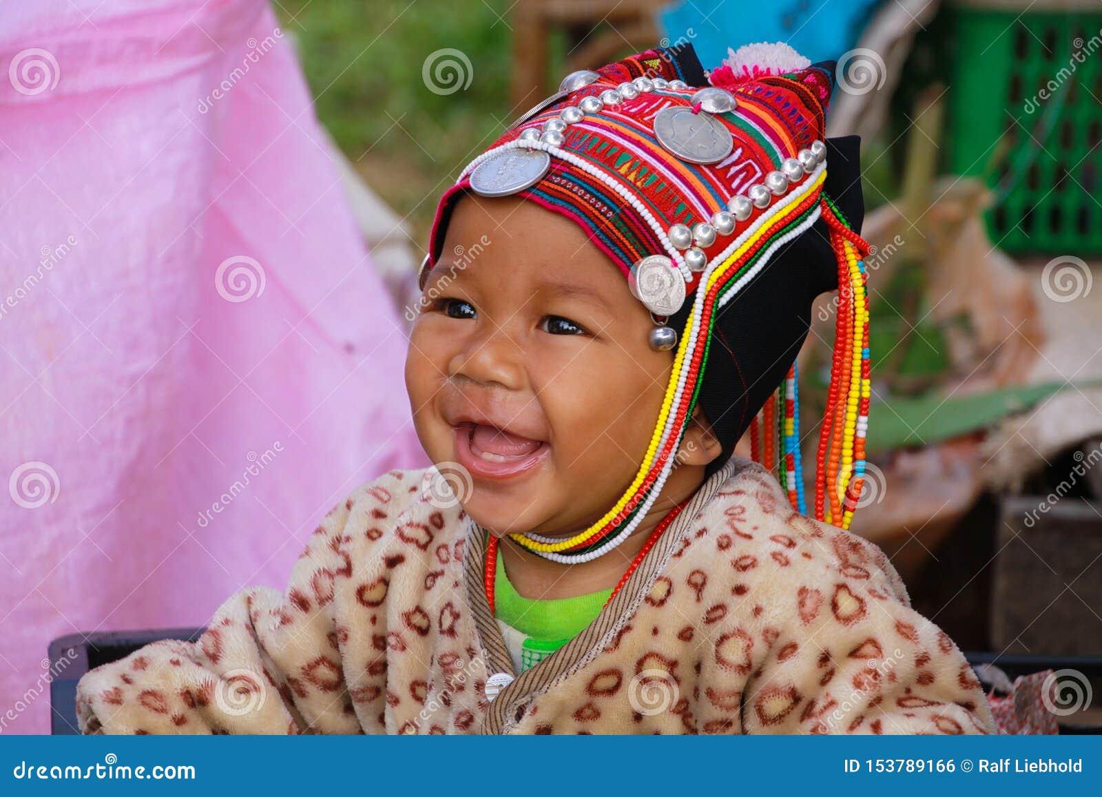 MAE SALONG, THAILAND - 17. DEZEMBER 2017: Porträt eines glücklichen Kleinkindbabys von Akha-Bergvolk in einem Einkaufskasten auf
