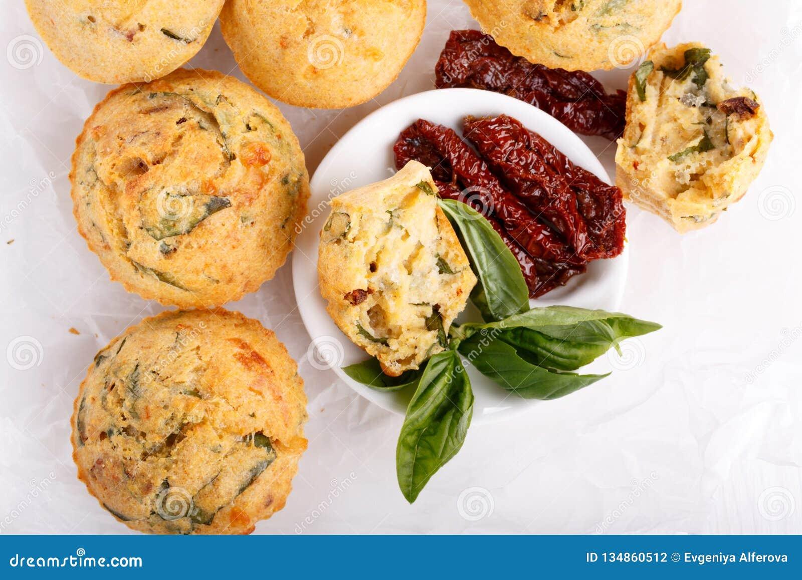 Maffins saborosos do queijo com manjericão e o tomate sol-secado