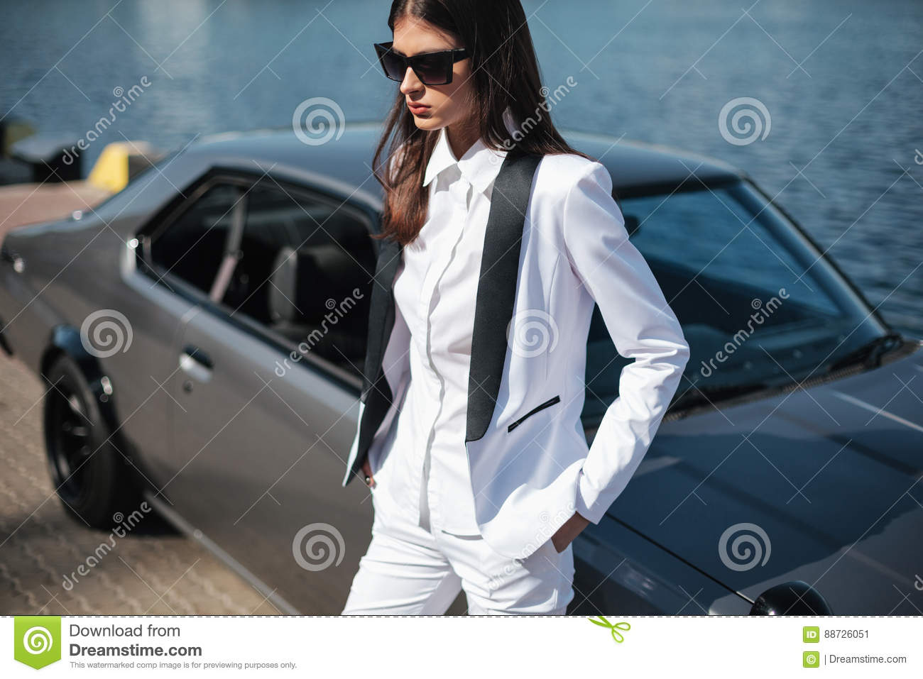 Mafia lady outside japanese car in the sea port. Fashion girl standing next to a retro sport car on the sun