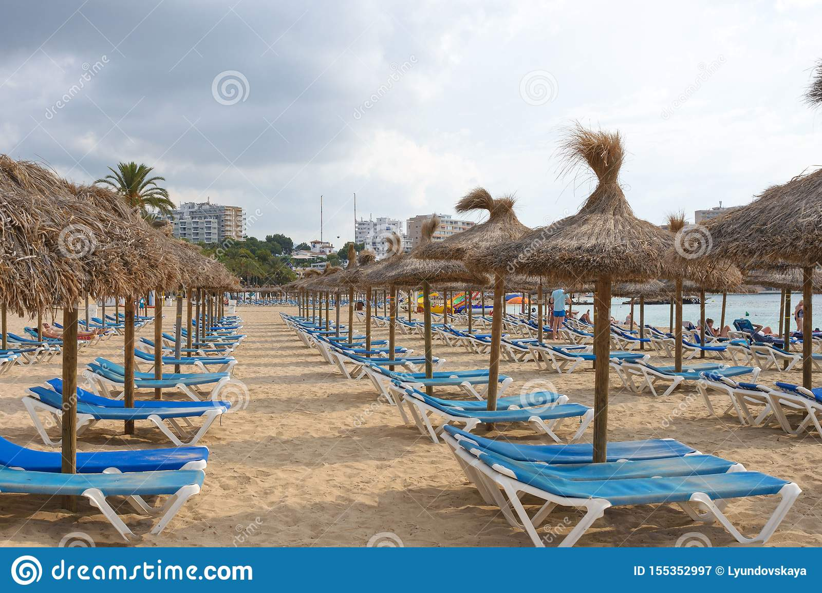 Mallorca traditional thatched umbrellas and blue sunbeds on the sandy beach of Magaluf resort. Balearic Islands