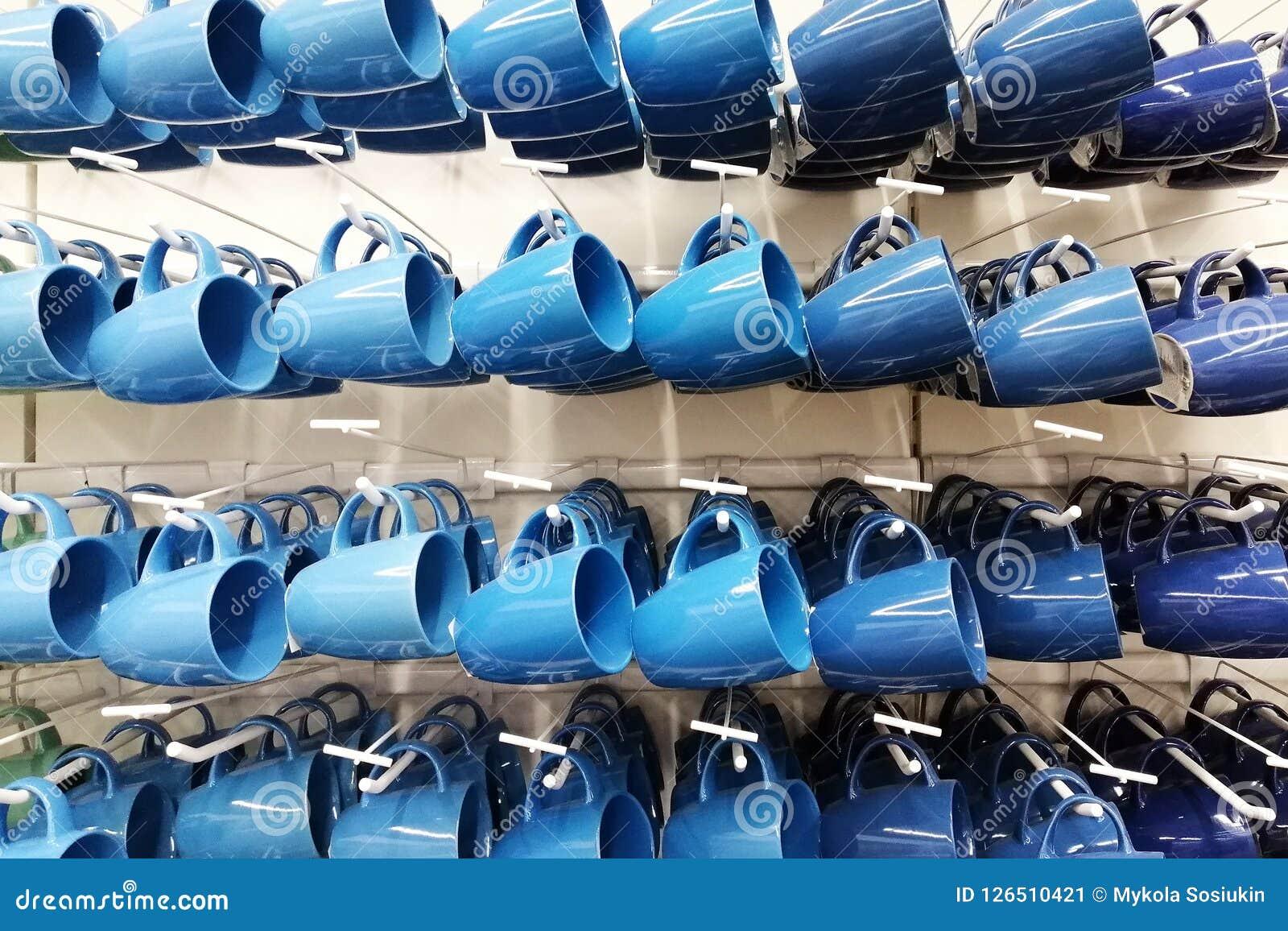 Magasin coloré de tasse tasses de différentes couleurs se tenant dans la boutique