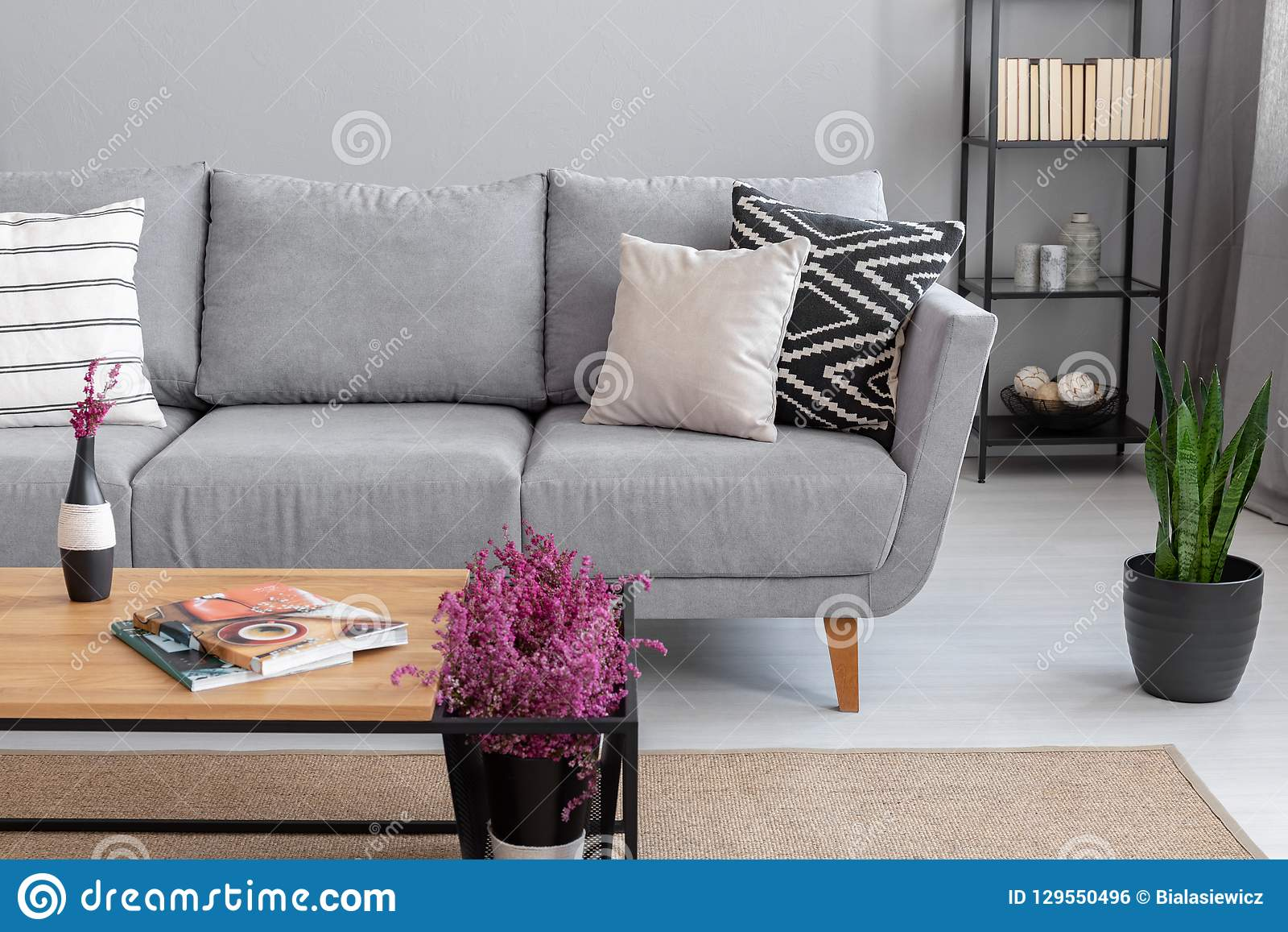 Magazines and heather on the wooden table near comfortable grey sofa with pillows, real photo with copy space