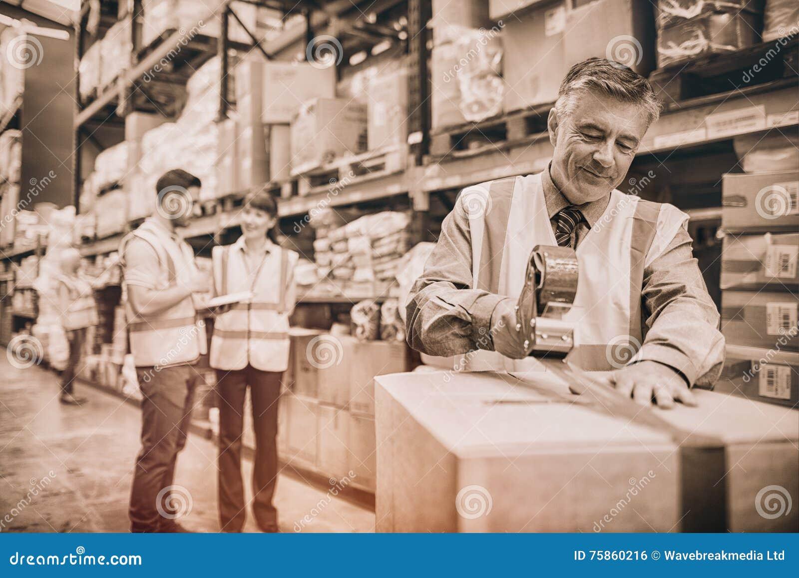 Magazynowego pracownika pieczęciowi kartony dla wysyłać