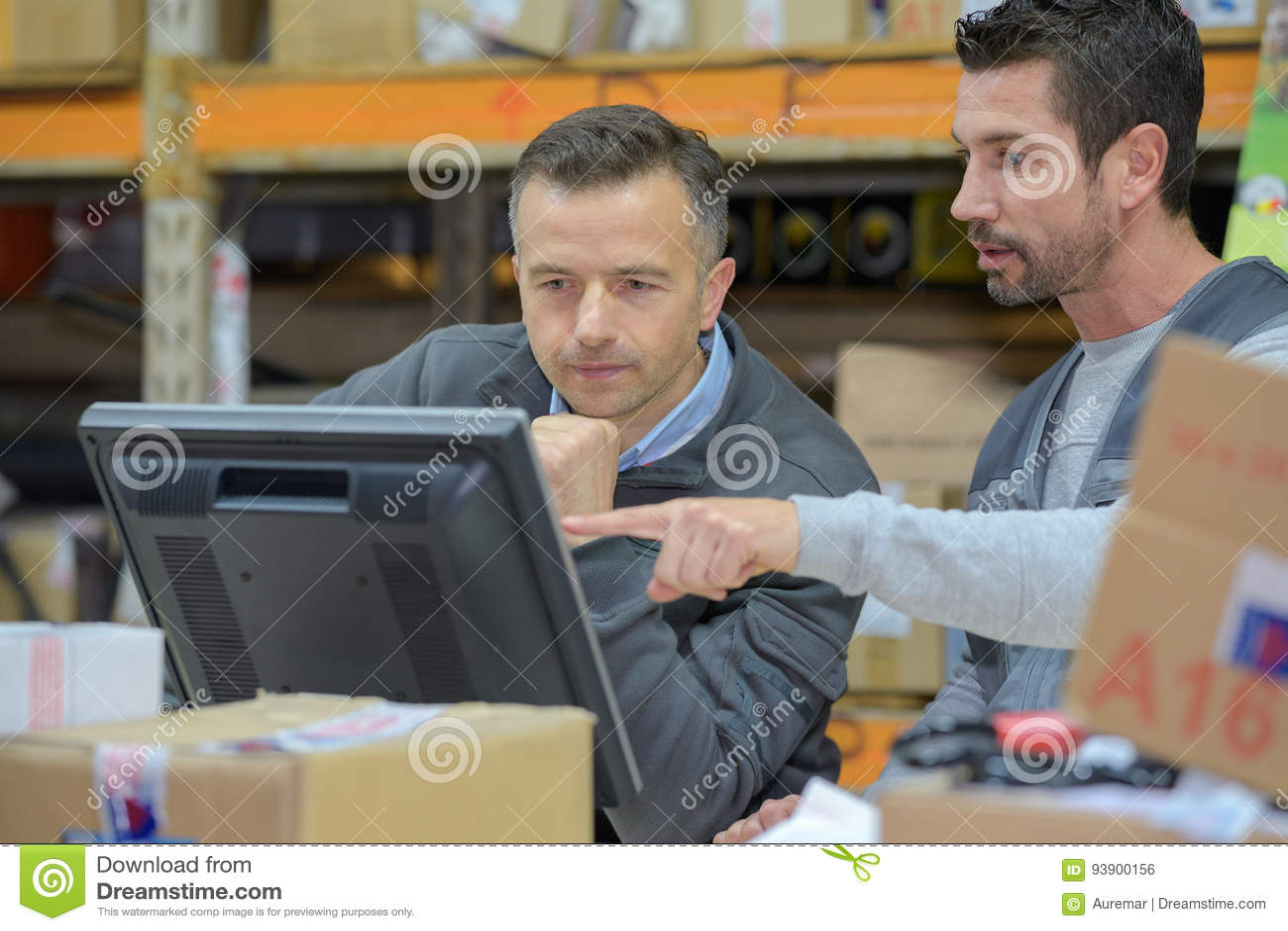 Magazynowy pracownik i kierownik używa komputer w magazynie