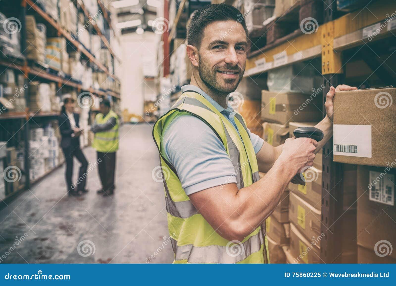 Magazynowy pracownika skanerowania pudełko podczas gdy ono uśmiecha się przy kamerą