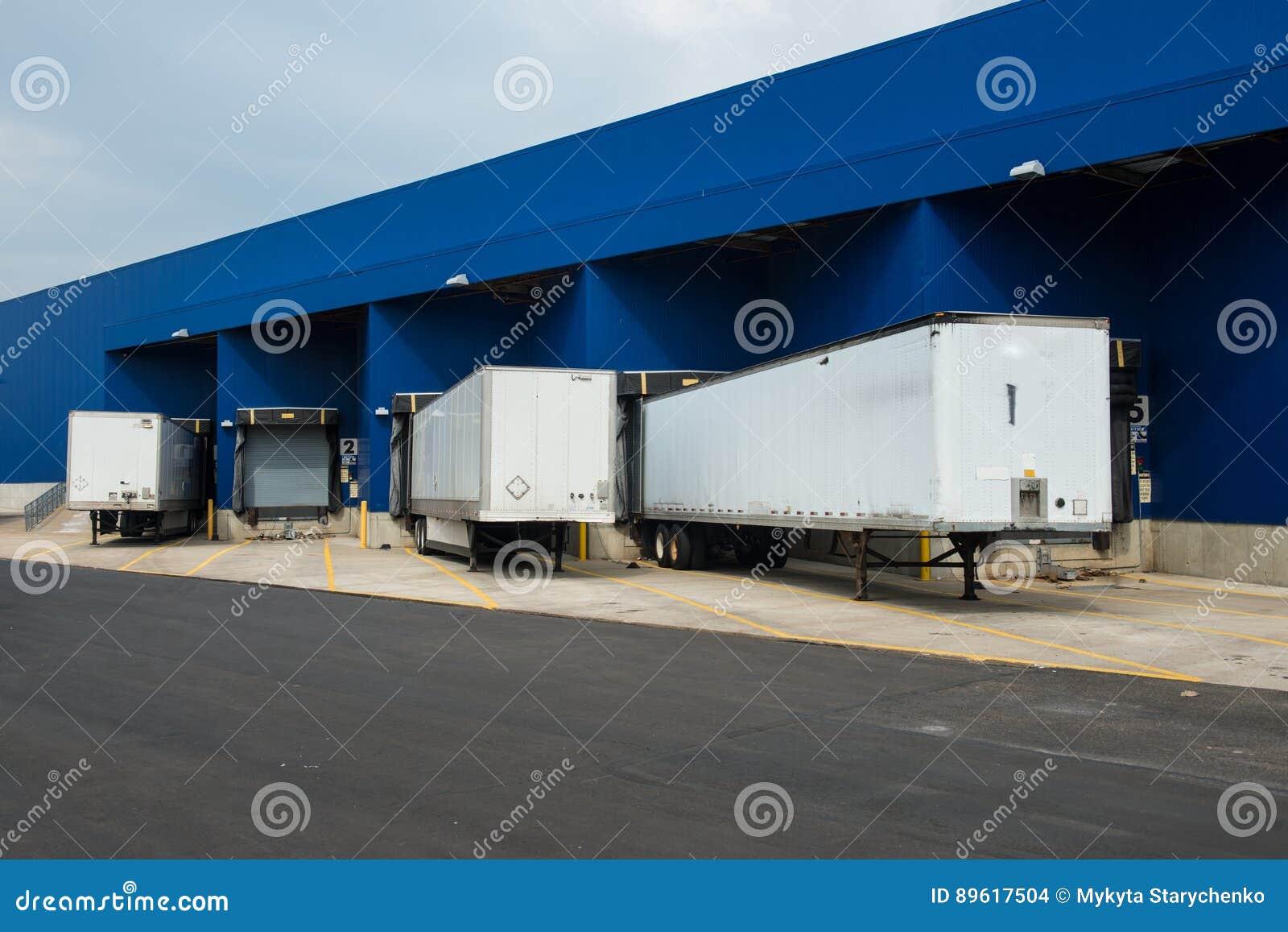 Magazzino di distribuzione grande con i portoni per i carichi ed i camion