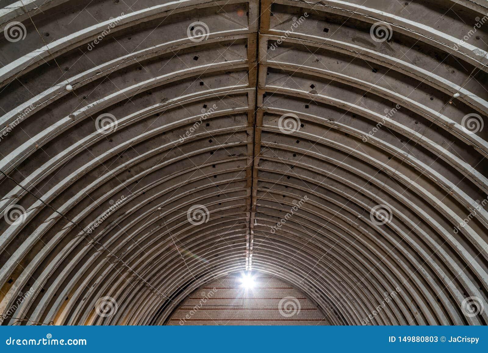 Magazzino vuoto abbandonato, vecchia costruzione metallica rustica con il tetto del metallo, interno di vecchia costruzione comme