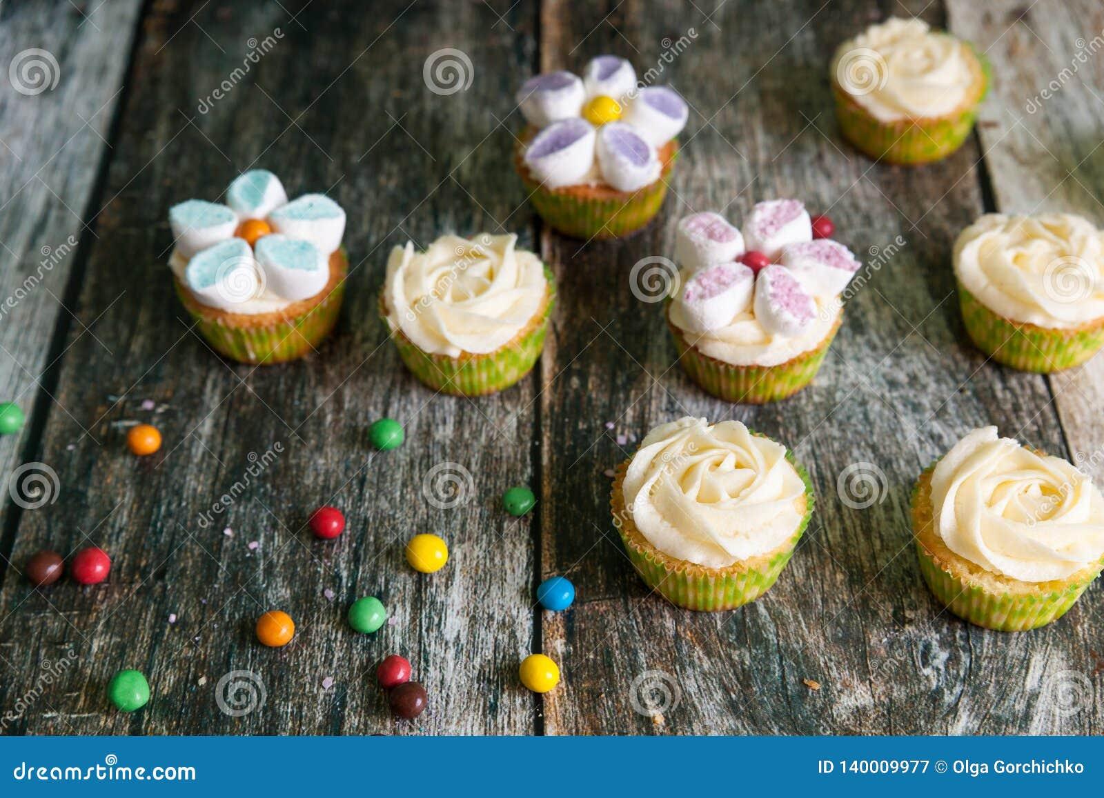 Magdalenas adornadas con las flores de la crema y de la melcocha de la mantequilla