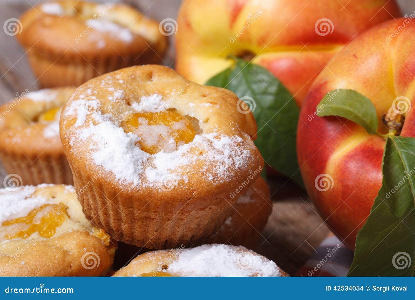 Magdalenas deliciosas con el melocotón asperjado con el azúcar en polvo