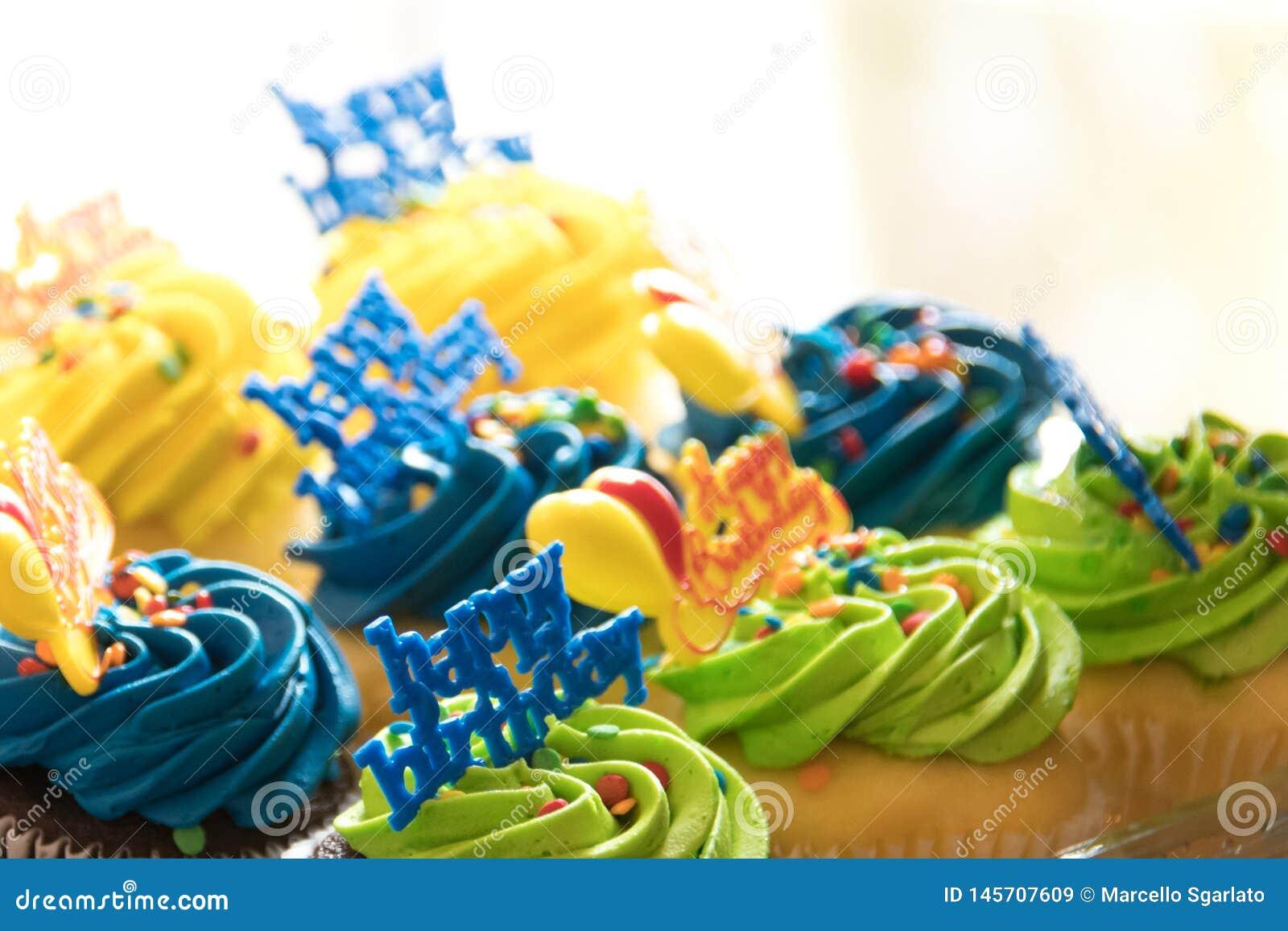 8 magdalenas multicoloras del feliz cumpleaños bordearon con confeti en colores pastel asperjan