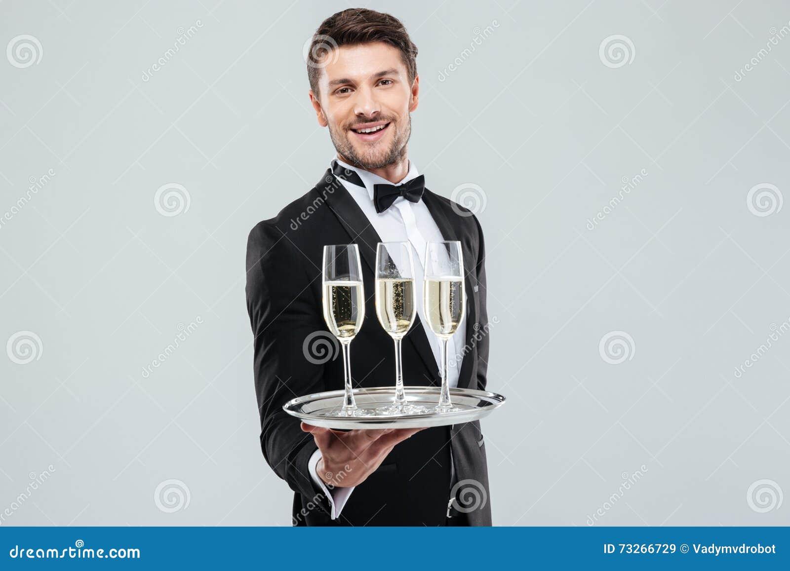 Maggiordomo allegro in champagne sorridente e d offerta dello smoking
