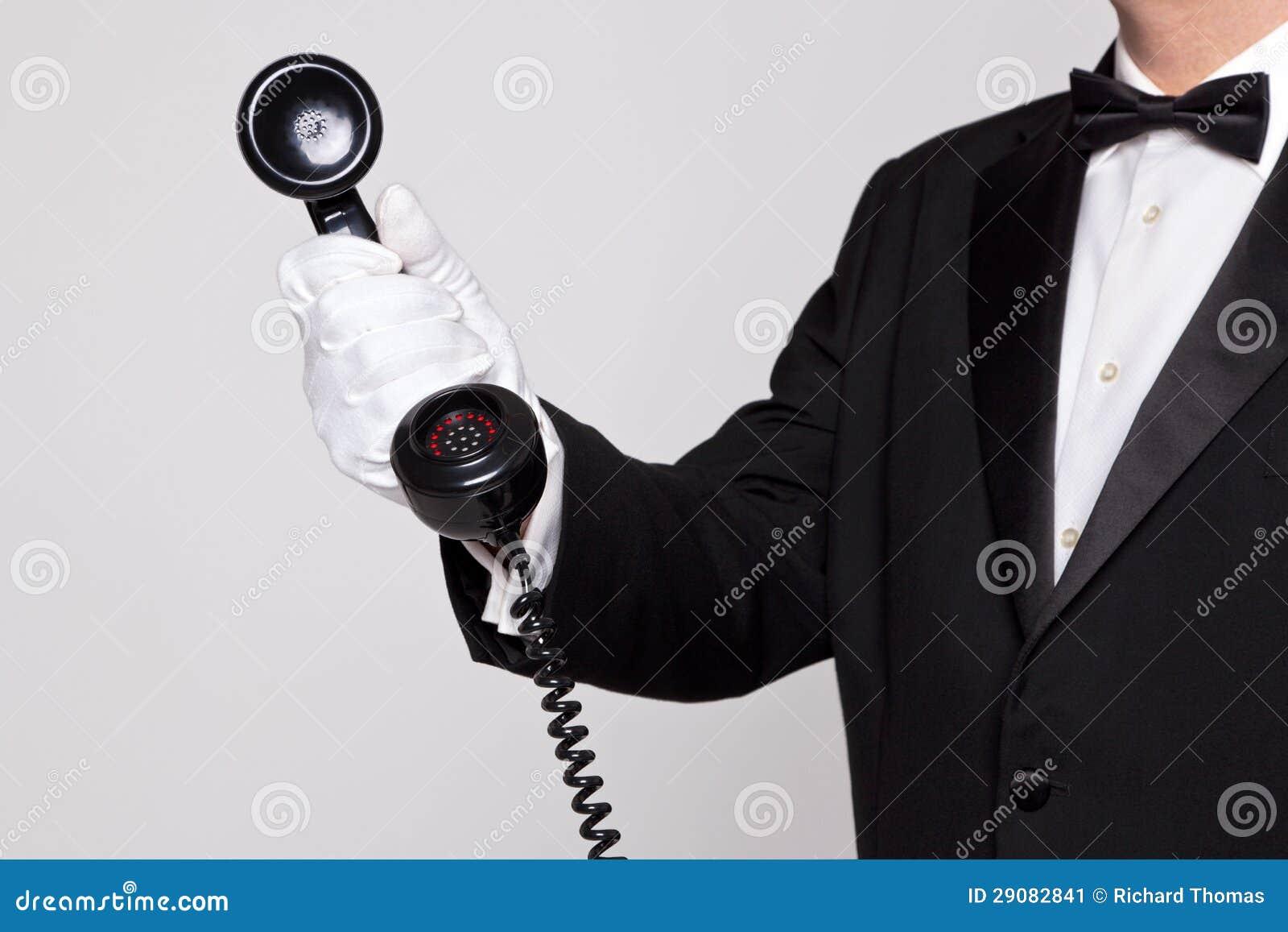 Maggiordomo che tiene un microtelefono del telefono