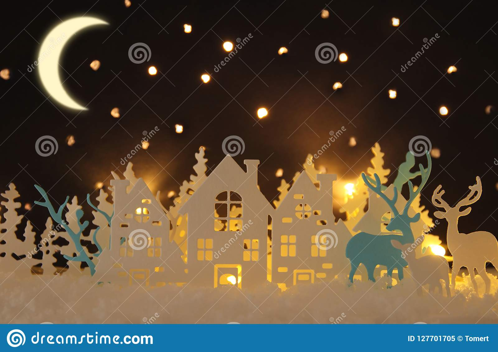 Magical Christmas paper cut winter background landscape with houses, trees, deer and snow in front of night starry sky background.