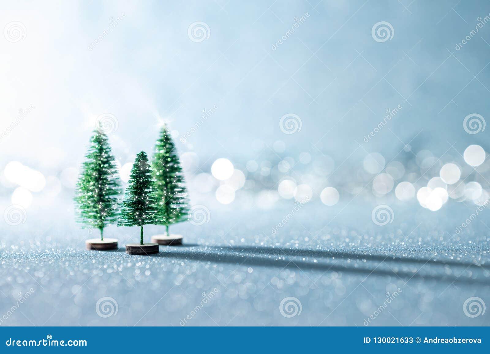 Magical Miniature Winter Wonderland Background Evergreen Christmas Trees On Shiny Blue Background With Bokeh Stock Image Image Of Festive Lights 130021633