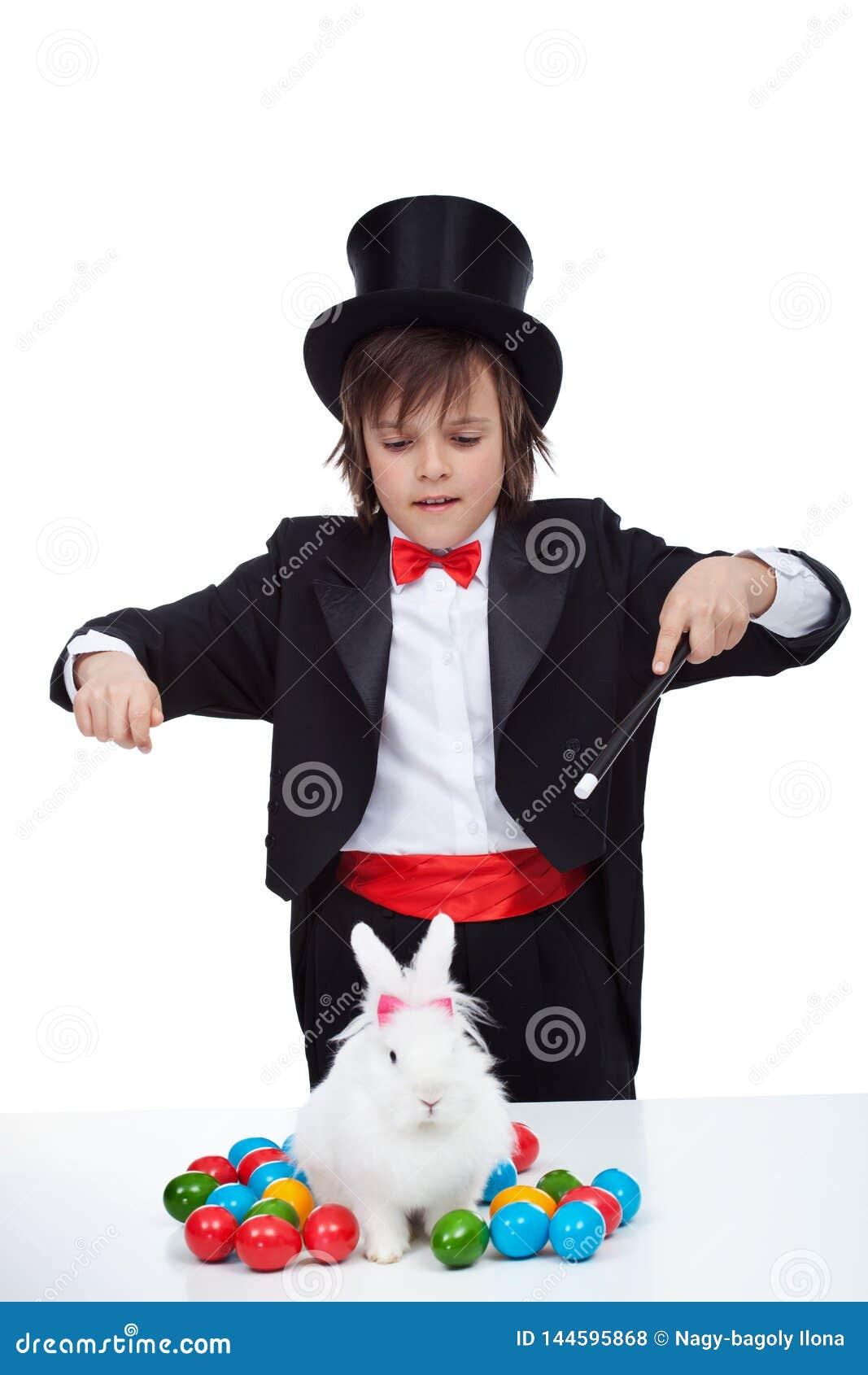 Magik chłopiec wykonuje magiczną sztuczkę z Easter królikiem i niektóre kolorowymi jajkami