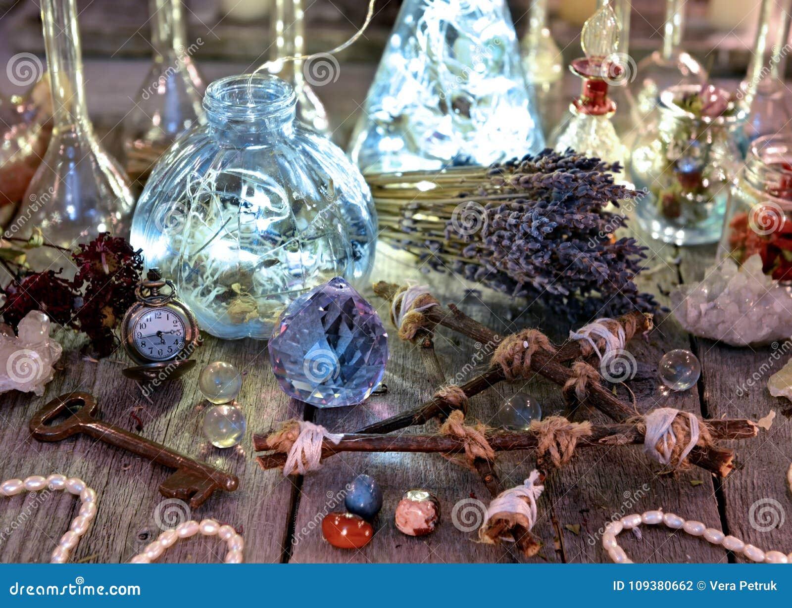 Magische Flaschen mit Lichtern, Pentagram, Kristall und Ritualgegenständen auf Hexentabelle