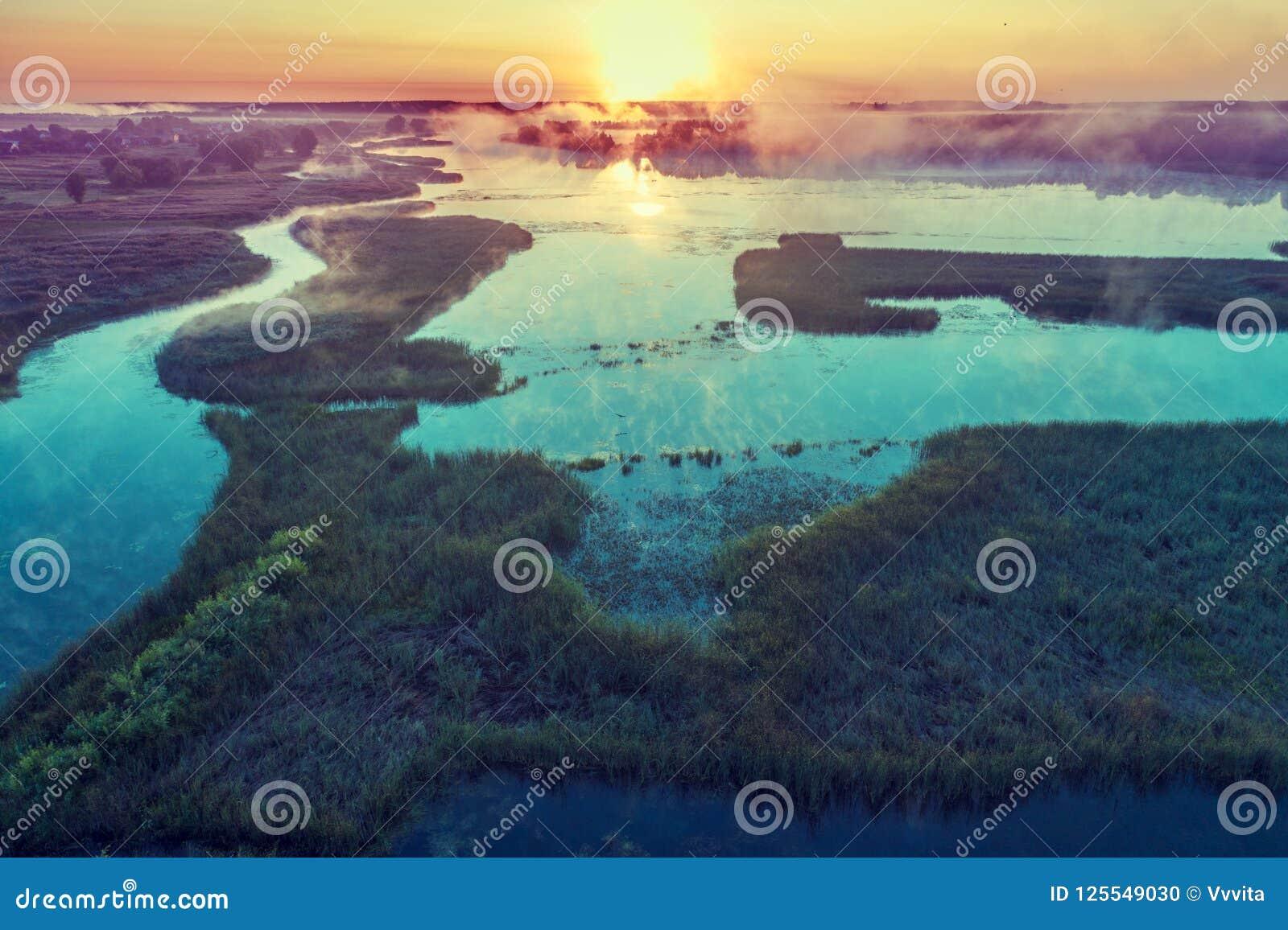 Magische nevelige zonsopgang over de rivier Lucht Mening