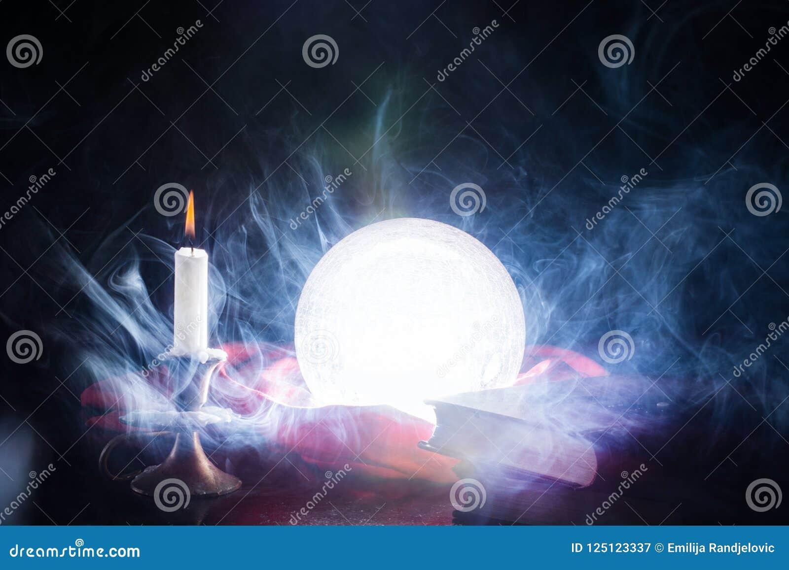 Magiska crystal ljus klumpa ihop sig på tabellen med stearinljuset i ljusstake och böcker