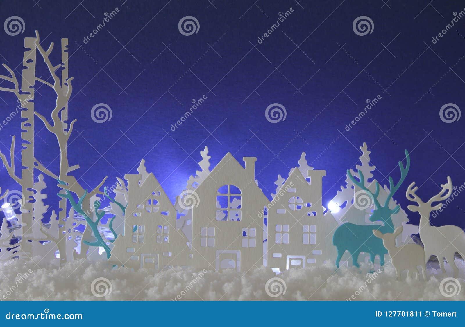 Magiskt landskap för bakgrund för vinter för julpapperssnitt med hus, träd, hjortar och den insnöade framdelen av bakgrund för vi