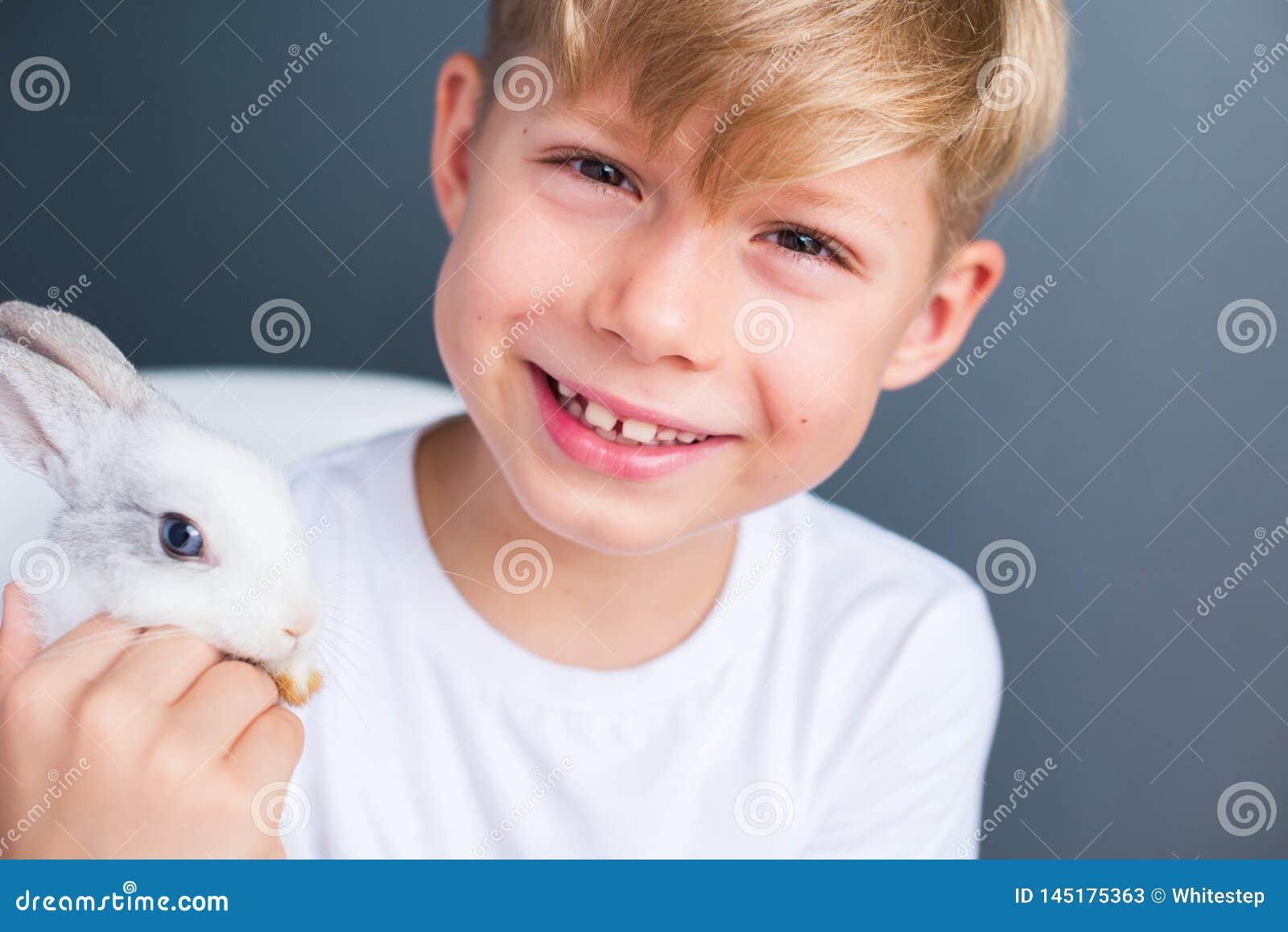 Maglietta bianca del ragazzino e coniglio dwarfish addomesticato