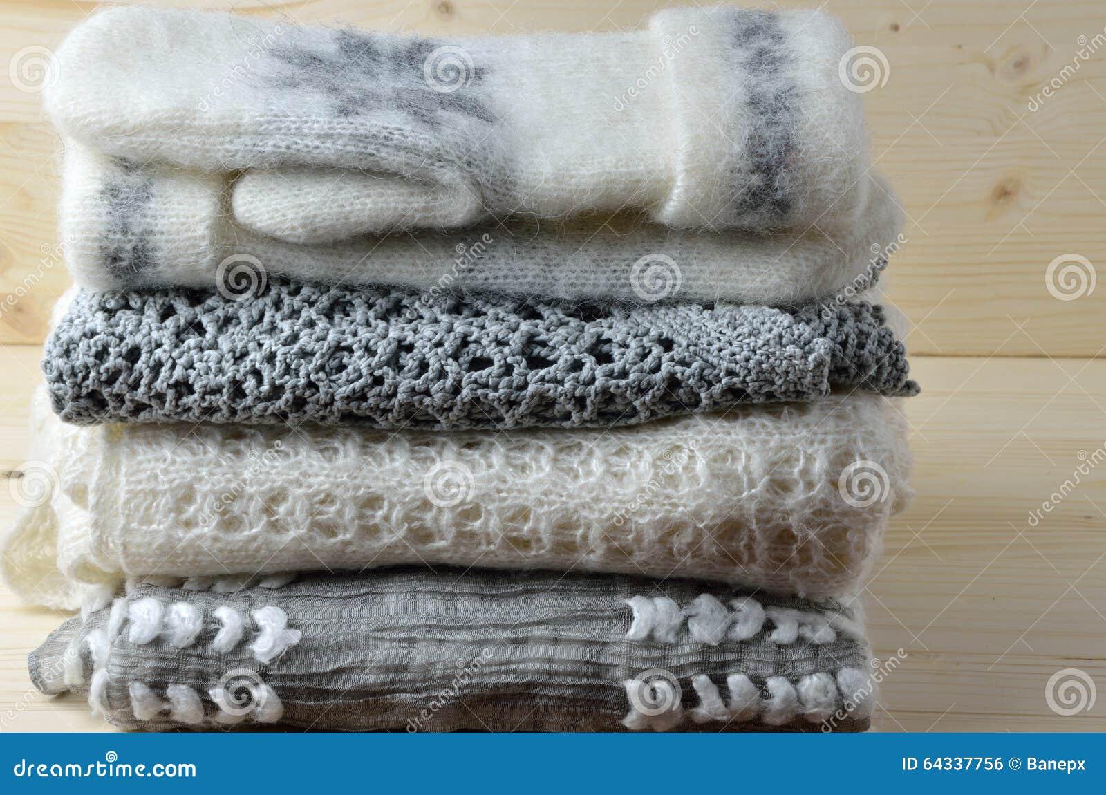 Maglioni, sciarpa e guanti di lana grigi e bianchi