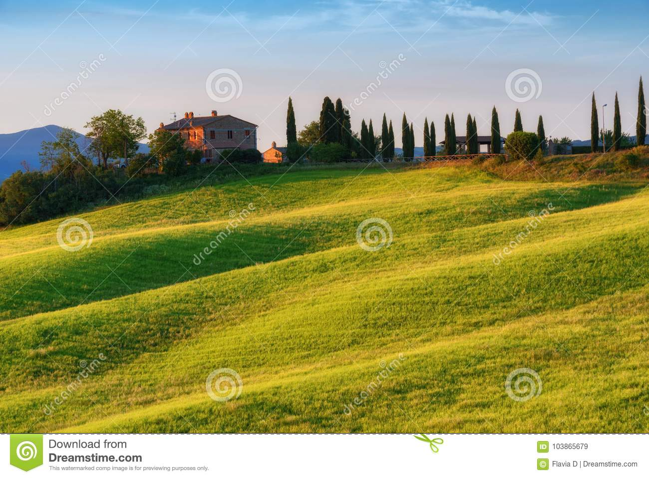 Magnificent spring landscape at sunrise.Beautiful view of typical tuscan farm house, green wave hills.