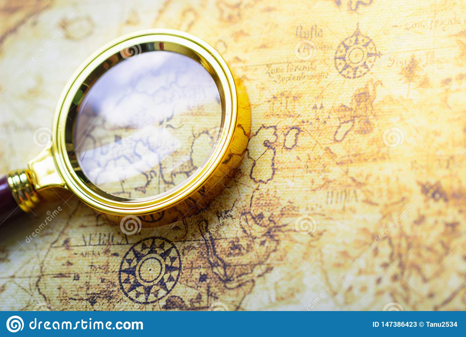 Magnifier on old map background.