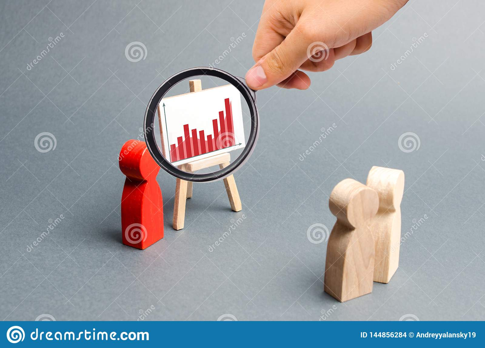 Magnifying glass is looking at the businessman reports to his staff at a briefing, a discussion of the business strategy