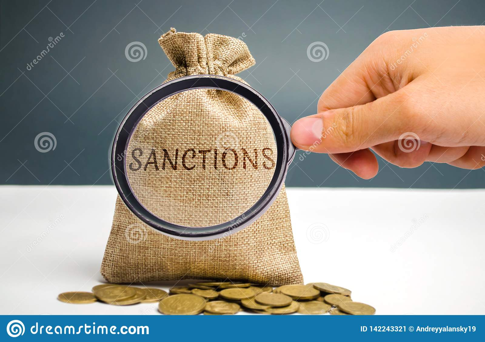 A magnifying glass is looking at a money bag with the word Sanctions. The imposition of economic and political sanctions on the