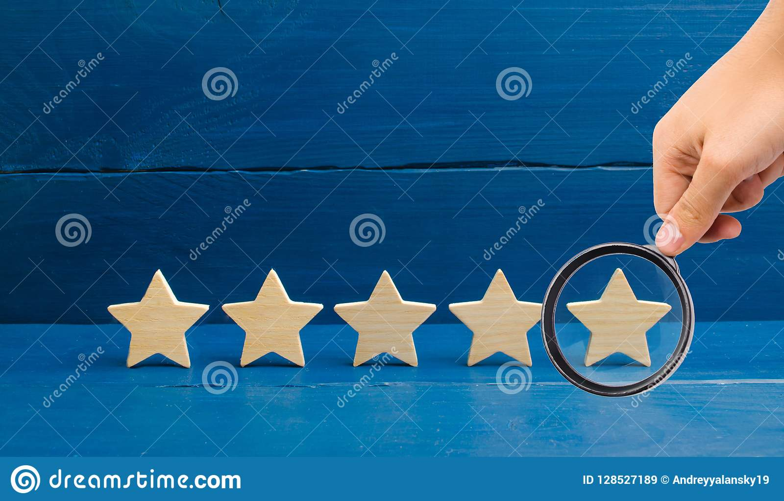 Magnifying glass is looking at the rating of the hotel, restaurant, mobile application.Five stars on a blue background. The concep