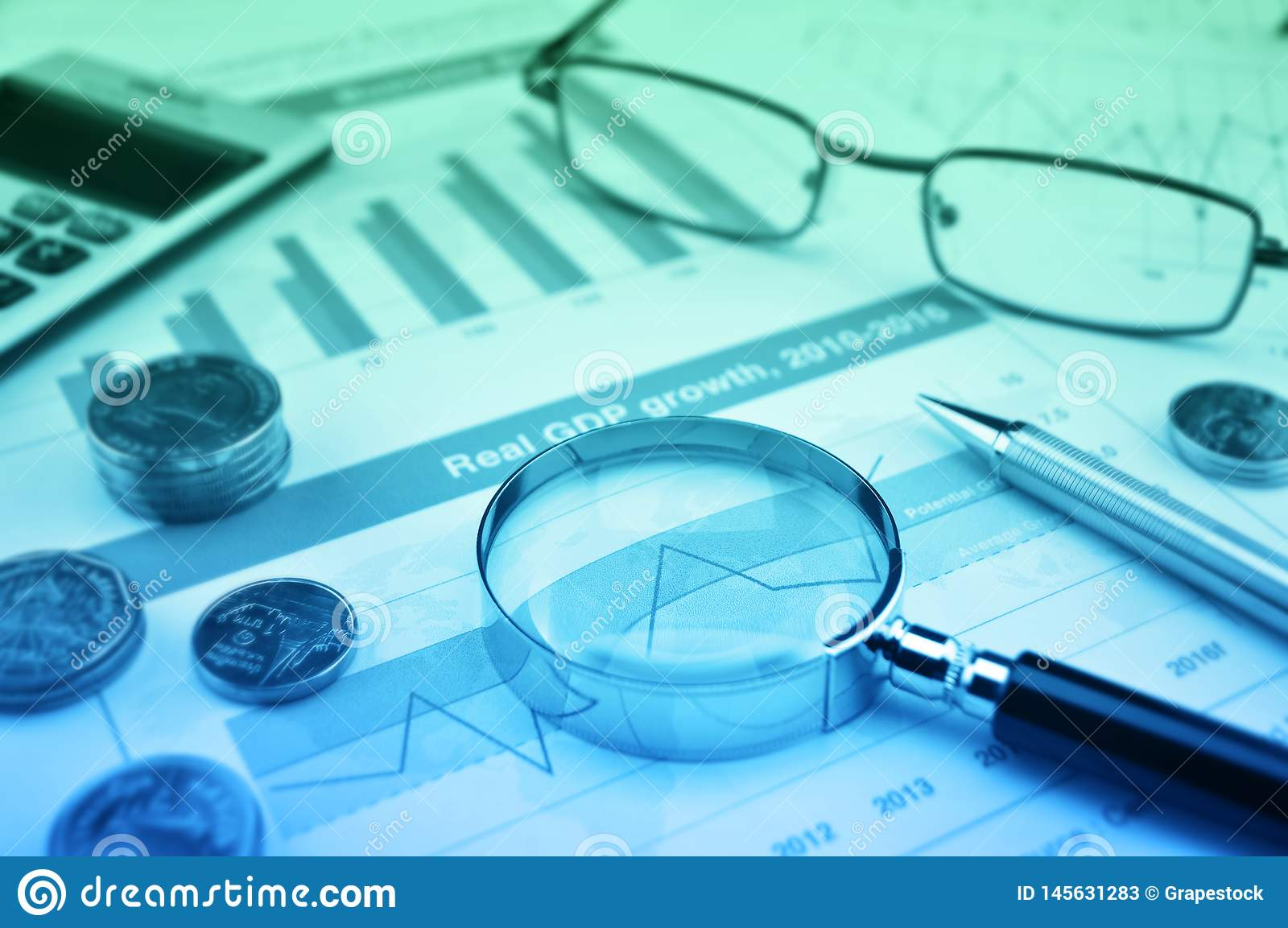 Magnifying glass, pen, coins, calculator and glasses on growth financial graph, Business success concept