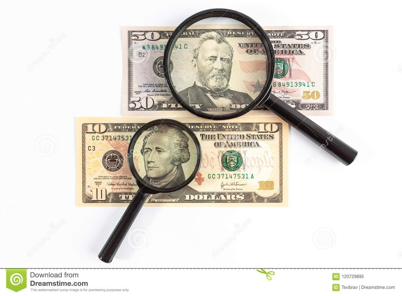 Magnifying glass placed on US dollar bills.