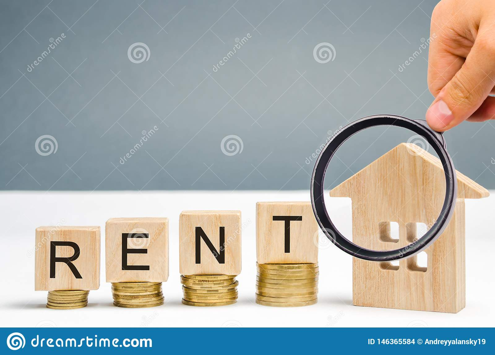 Magnifying glass, wooden blocks with the word Rent, coins and a miniature house. The concept of renting housing and real estate.