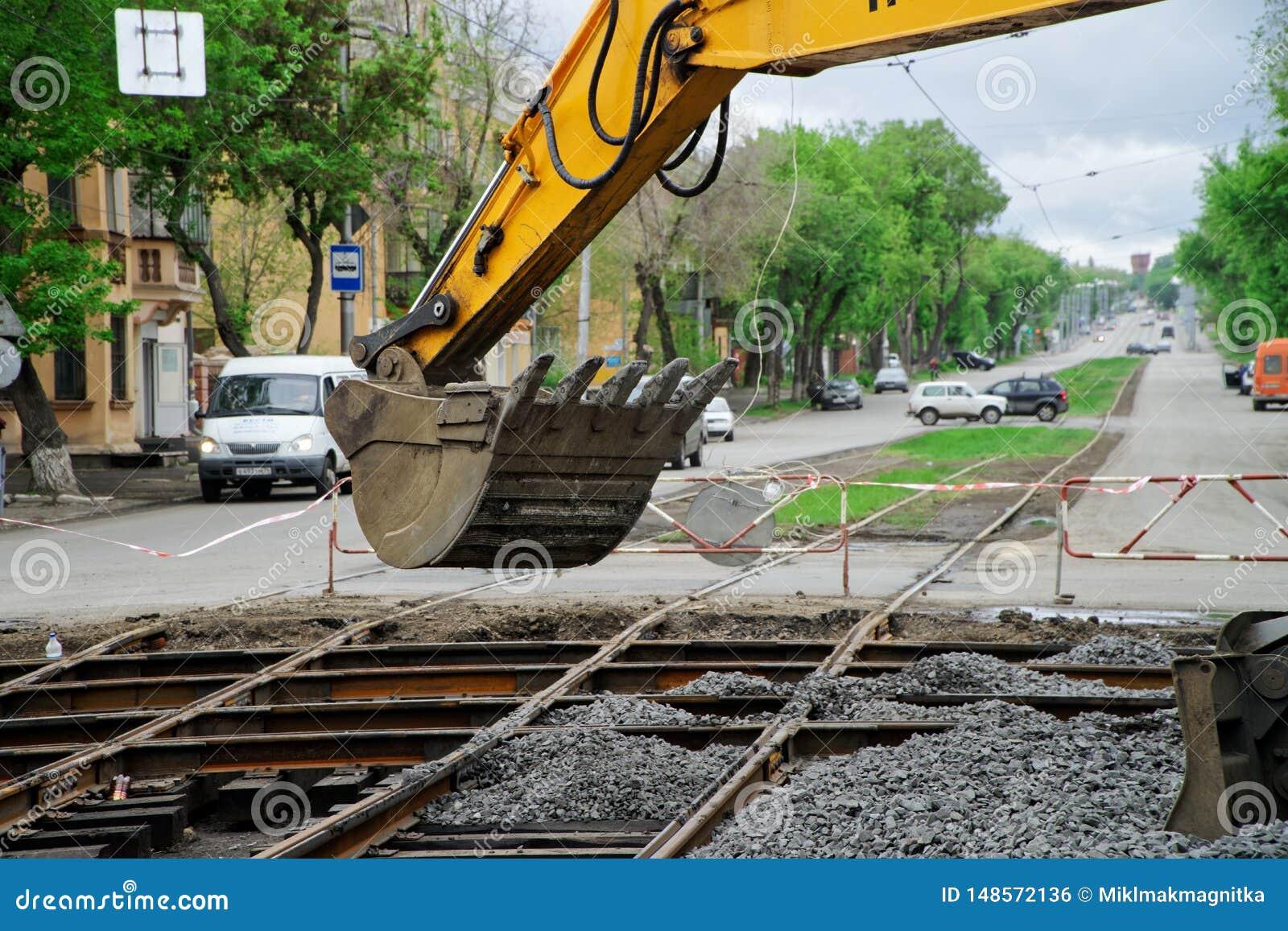 Magnitogorsk, R?ssia, - maio, 17, 2019 A cubeta da entulho adormecida de queda da máquina escavadora amarela reparou os trilhos d