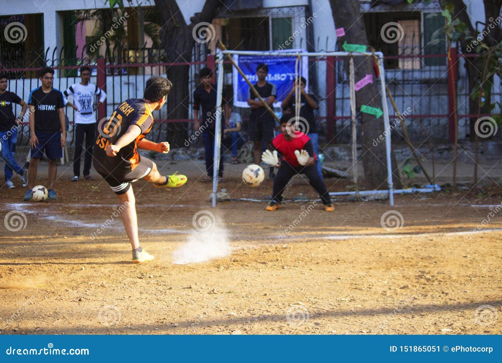 MAHARASHTRA, ÍNDIA, em fevereiro de 2019, meninos de Yong que batem o pontapé de grande penalidade durante o fósforo de futebol