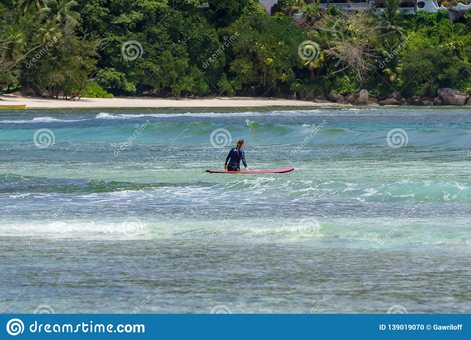 MAHE, SEYCHELLES - SEPTEMBER 25, 2018: Unidentified man surfing on a large wave on island Mahe on the coast of Indian ocean - is