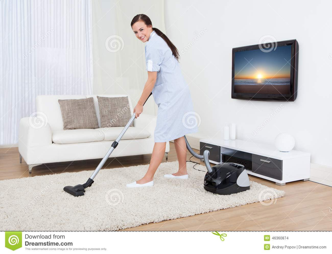 Maid Cleaning Carpet With Vacuum Cleaner Stock Photo