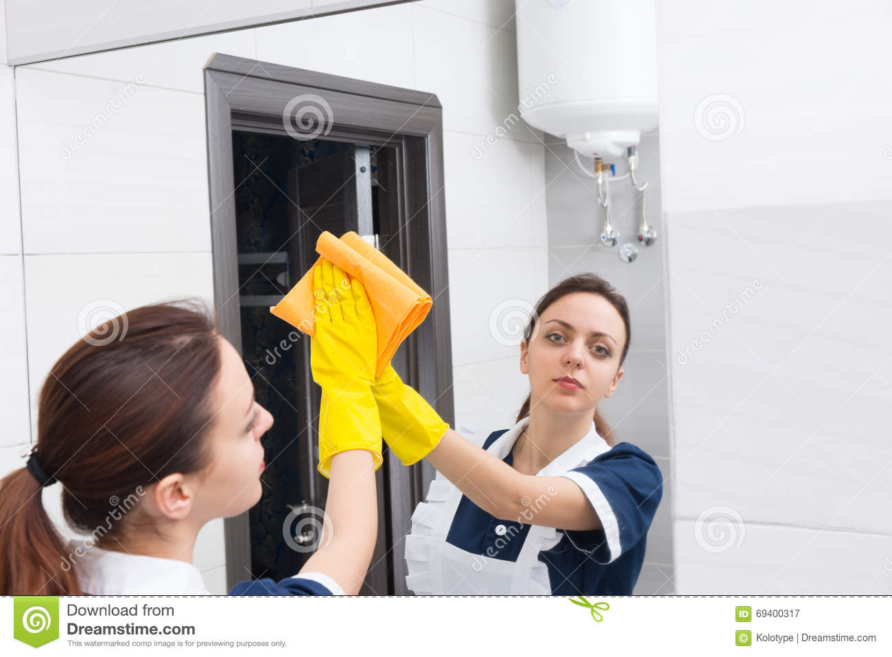 How to clean bathroom mirror - Maid Looking In Mirror While Cleaning Bathroom Royalty Free Stock Photography