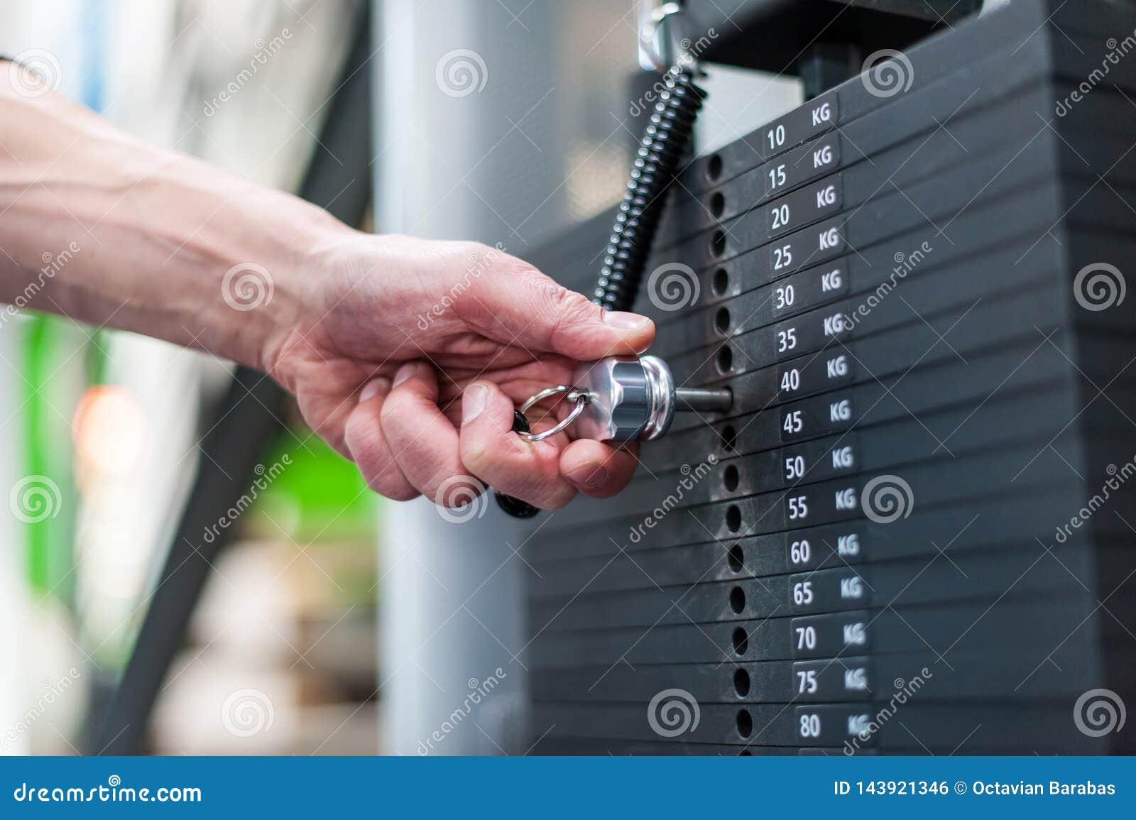 Main ajustant des poids au centre de fitness