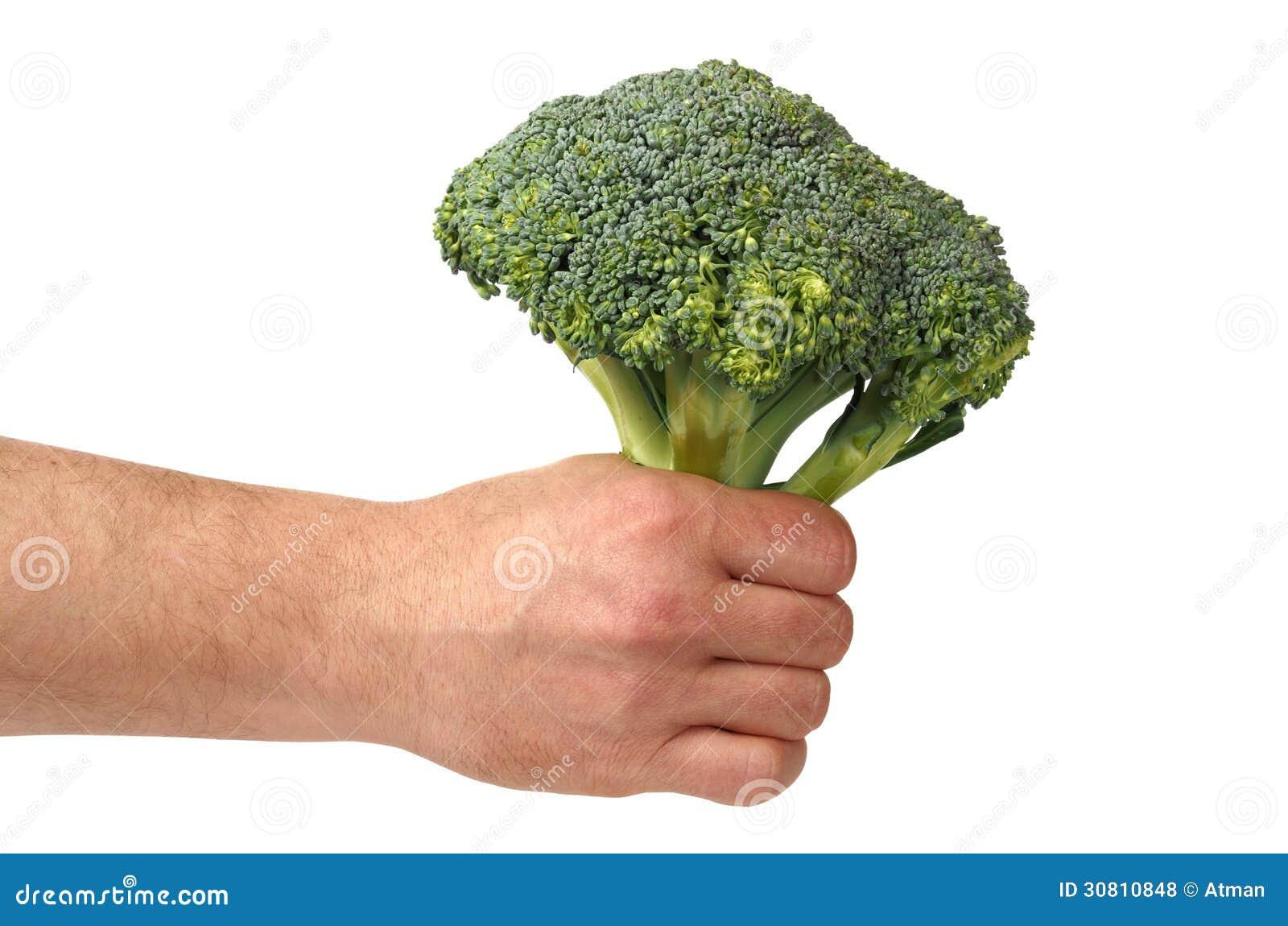 Main avec le brocoli sur le blanc
