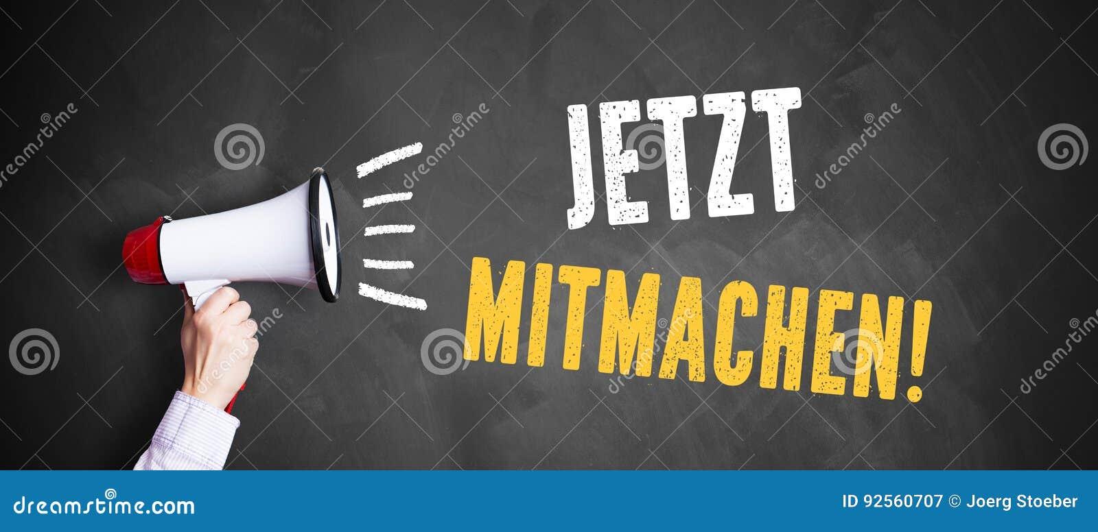 Main avec un mégaphone devant un tableau noir avec le ` allemand de s inscrire de ` de message