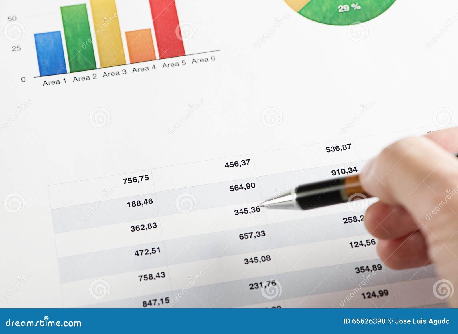 Main avec un stylo se dirigeant sur les graphiques colorés de finances