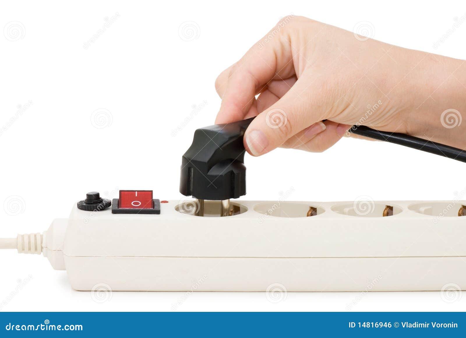 Main avec une fiche électrique et un plot